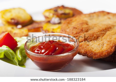 ketchup with a wiener schnitzel and roasted potatoes  - stock photo