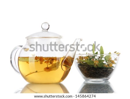 Kettle and bowl of tea with linden on  wooden table nature background - stock photo
