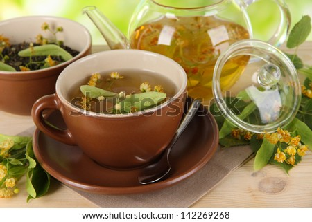 Kettle and cup of tea with linden on  wooden table on nature background
