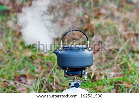 Kettle boiling over gas burner on the nature - stock photo