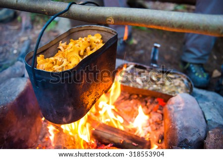 Kettle full of mushrooms on the fire - stock photo