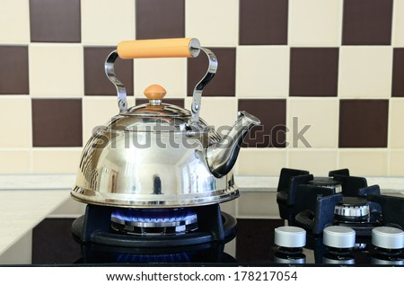 Kettle heats the gas stove. Interior of modern kitchen - stock photo