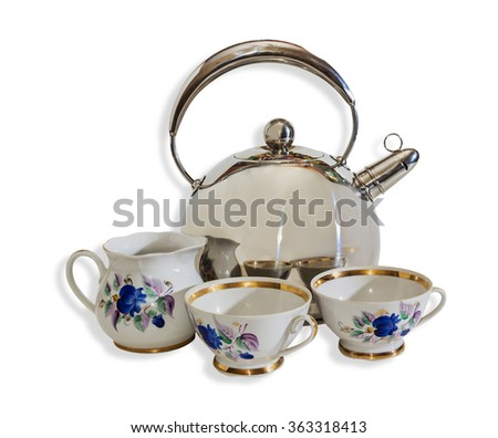 Kettle in stainless steel with a whistle, porcelain jug and cups on a light background. Isolation.