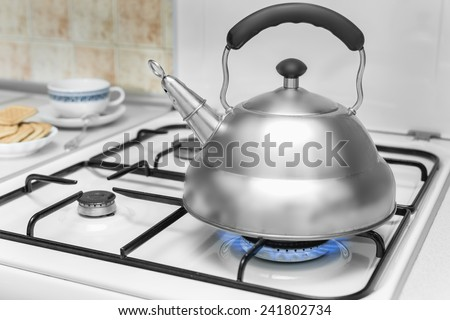 kettle on a gas stove flame burn not boiling - stock photo