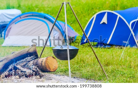 kettle on a tripod hanging around a bonfire - stock photo