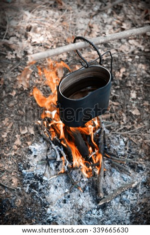 Kettle on fire in the forest - stock photo