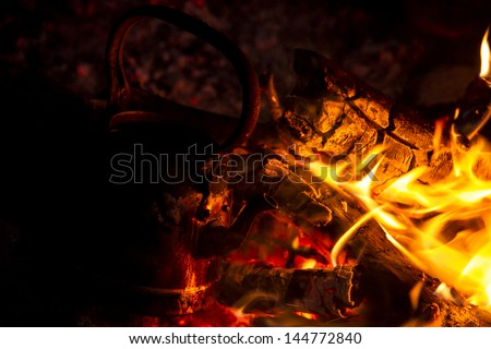 kettle on the fire at night to boil some water - stock photo