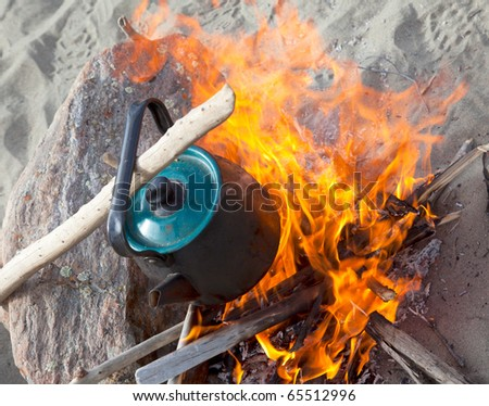 Kettle on the fire. Winter day in a campaign - stock photo