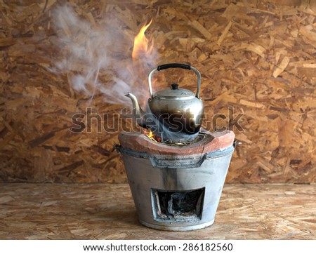 Kettle on the fireplace, on wooden background, Still life style - stock photo