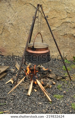 Kettle over the fire and smoky, delicious mushroom goulash inside - stock photo