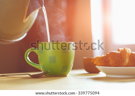 kettle pouring boiling water into a cup during breakfast in morning sunlight - stock photo