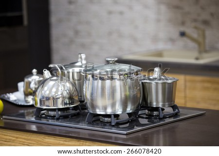 kettle, stainless steel pan on gas cooker top view  - stock photo