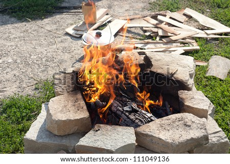 kettle with boiling soup over campfire
