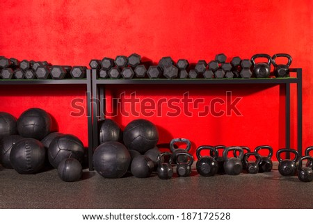 Kettlebell dumbbell and weighted slam balls weight training equipment at gym red walls - stock photo
