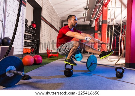 kettlebell man pistol squat balance at gym workout - stock photo
