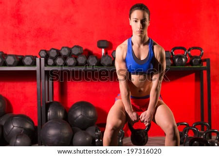 Kettlebell swing workout training woman at gym with red walls - stock photo