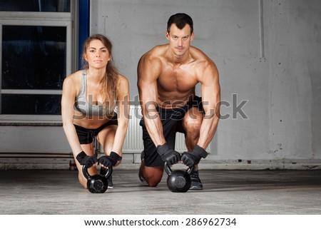 kettlebell training man and woman - stock photo