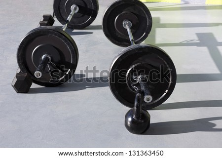 Kettlebells at crossfit gym with lifting bar weights fitness equipment - stock photo