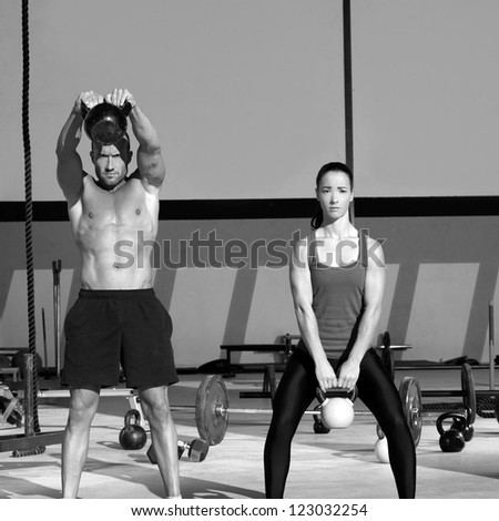 Kettlebells swing exercise man and woman workout at gym - stock photo