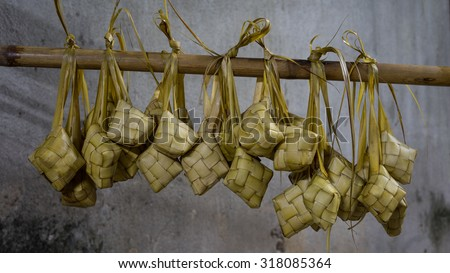 Ketupat, Kupat or Tipat is a type of dumpling made from rice packed inside a diamond-shaped container of woven palm leaf pouch. It is commonly found in Indonesia, Malaysia, Brunei and Singapore. - stock photo