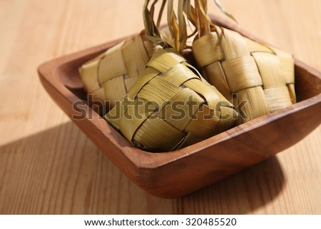 Ketupat (Rice Dumpling) On wooden Background. Ketupat is a natural rice casing made from young coconut leaves for cooking rice during eid Mubarak - stock photo