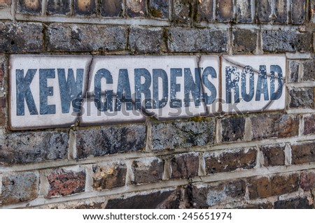 Kew Gardens Road sign on a brick wall.