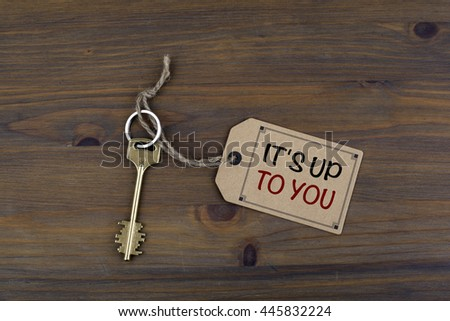 Key and a note on a wooden table with text - It's Up To You - stock photo