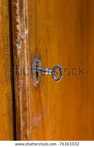 Key and door to an old wooden cabinet - stock photo