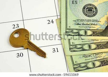 Key and money on a calendar concepts of paying the mortgage on time - stock photo