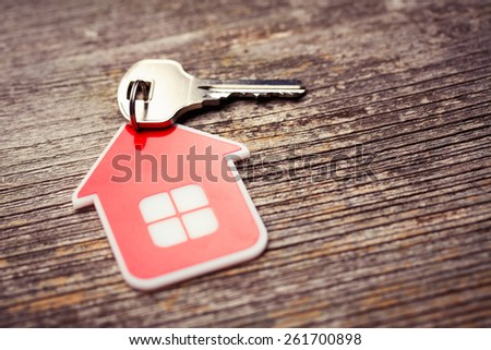 Key and Red House on Wood background