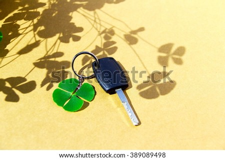 Key car and clover leaf. 4-leaf clover and car key on paperboard background with clover shadow. Conceptual image about lucky.    - stock photo