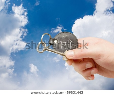 key chain in human hand on sky background