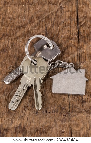 key for house on wooden surface - stock photo