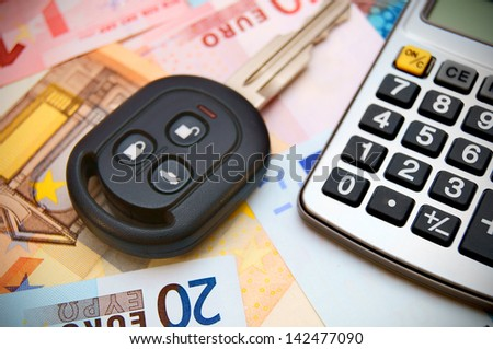Key from the car and the calculator for euro banknotes. - stock photo
