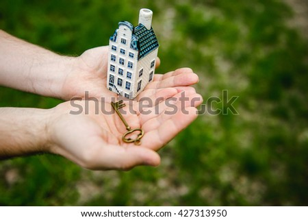 Key, House, Human Hand on a background of green grass. conceptual - stock photo