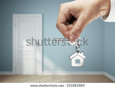 key in hand against the backdrop of the blue rooms - stock photo