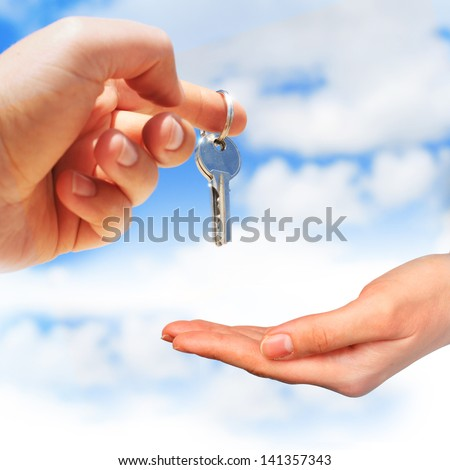 Key in hand over blue sky background.