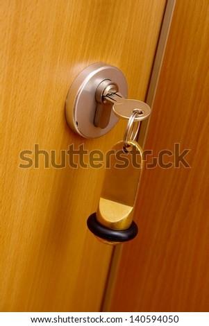 Key in the door of a hotel room - stock photo