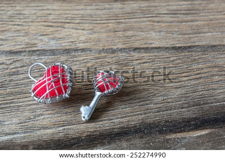 key iron heart and iron red heart on wooden background - stock photo