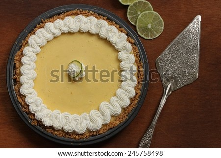 Key lime pie with cream topping and fresh limes - stock photo
