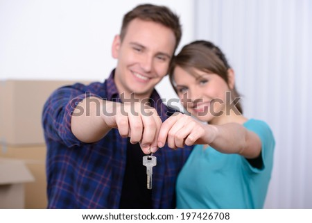 Key of their new house. Happy young couple standing close to each other and smiling while holding key from the house
