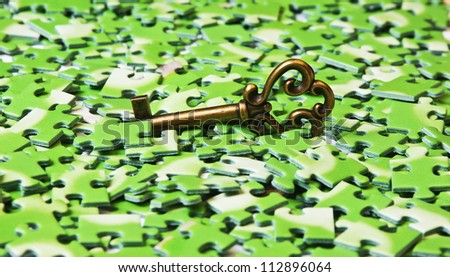 key on pile of green puzzle - stock photo