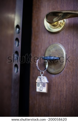 Key ring with house on the front door of an apartment - stock photo