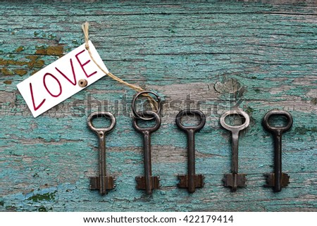 Key to love among other ones on old wooden background