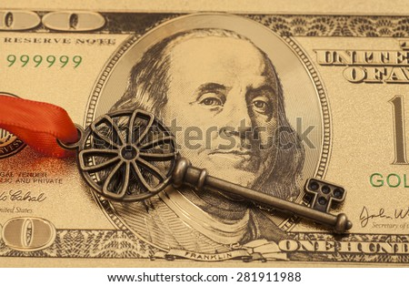 Key To Success With Red Bow on Golden hundred dollar bill - stock photo