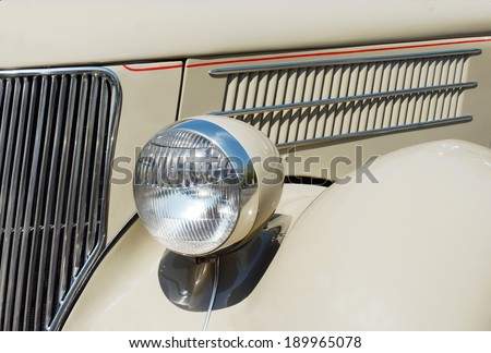 KEY WEST, FL-APRIL 27:  Closeup showing details of the headlamp, grill and vent on a beige 1936 Ford Touring Phaeton Convertible Sedan in Key West, Florida on April 27, 2014.  - stock photo