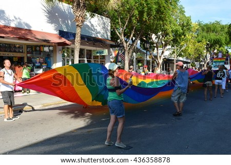 KEY WEST, FL-JUNE 12: People marching in the 2016 Key West Gay Pride parade carry a rainbow gay flag banner on Sunday, June 12, 2016, in Key West, Florida. - stock photo