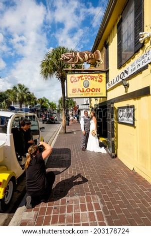 KEY WEST, FLORIDA USA - JUNE 26, 2014: A wedding party making a stop at the historic Captain Tony's Saloon in downtown Key West. - stock photo