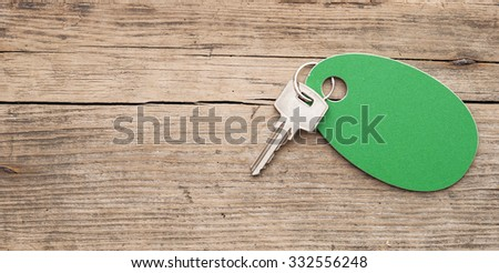 key with a blank label on an old wooden plank - stock photo