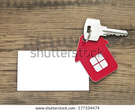Key with house icon and blank paper on wooden background   - stock photo